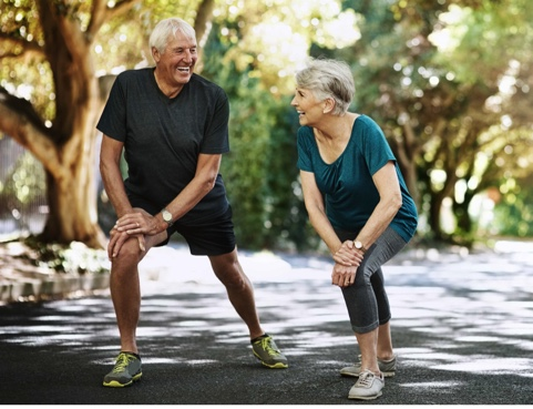 Older man and woman stretching outdoors